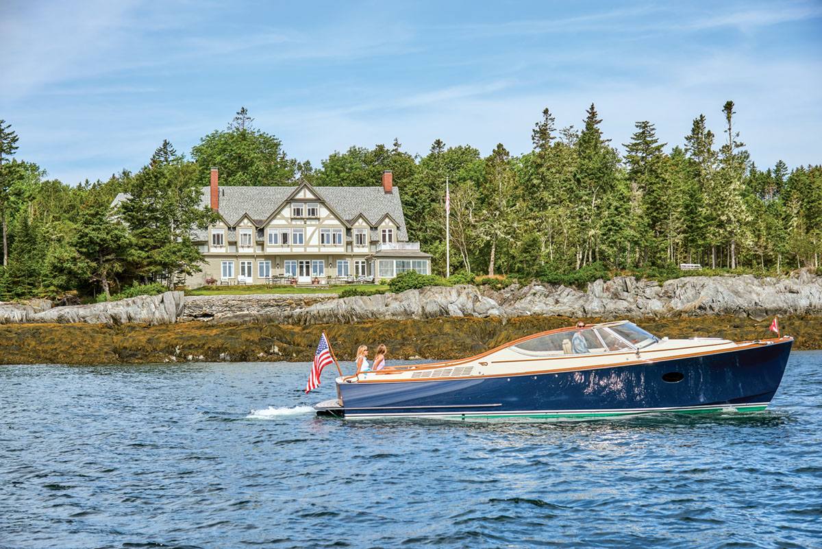 A speed boat with an American flag rides by a home on the Maine coast