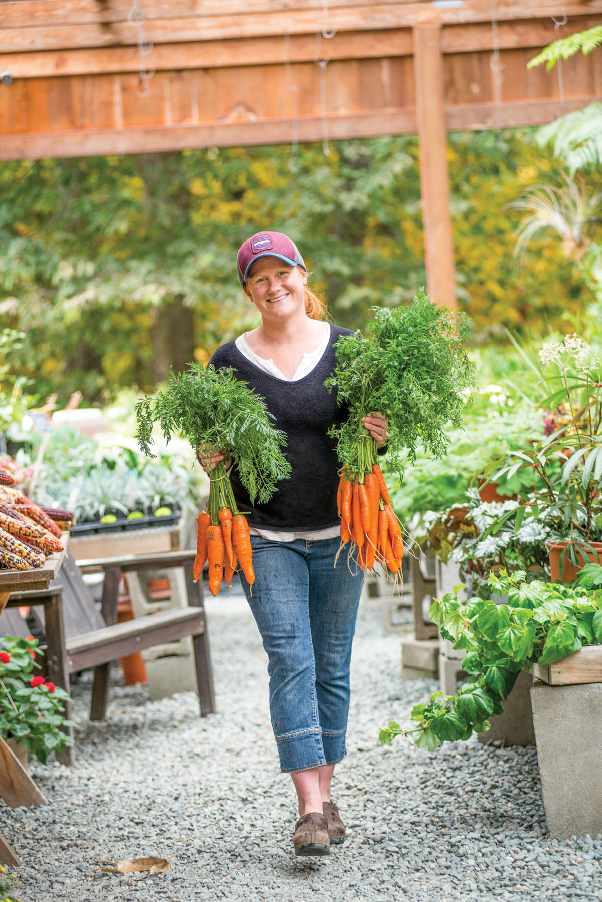 Allie Boeri, wearing her red hair in a ponytail under a ballcap, walks through the open-air farmers market carrying a bunch of carrots in each hand