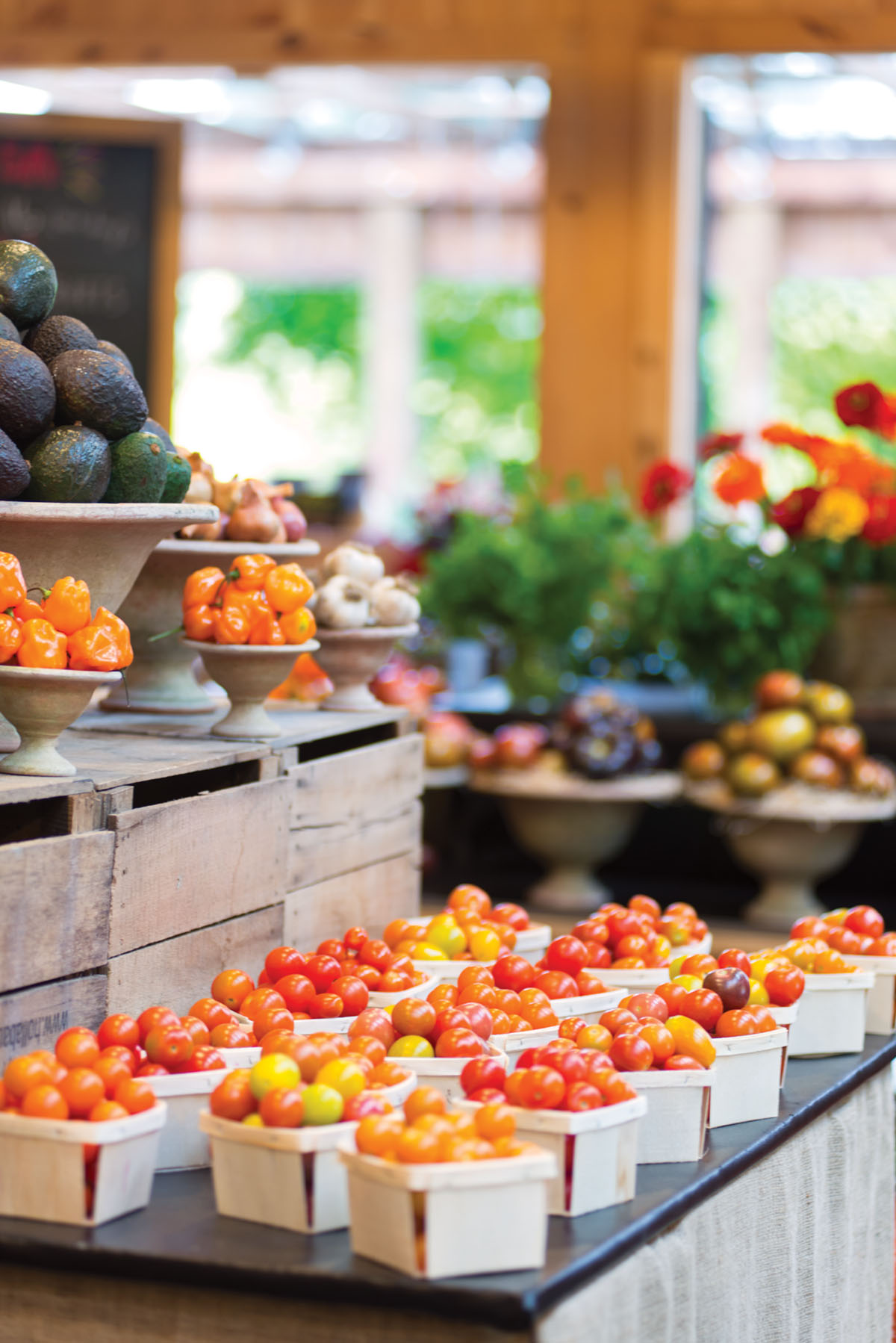 display of tomatoes in quart sized containers. Above, compote bowls stacked on wooden crates display peppers, garlic heads, shallots, and avocados