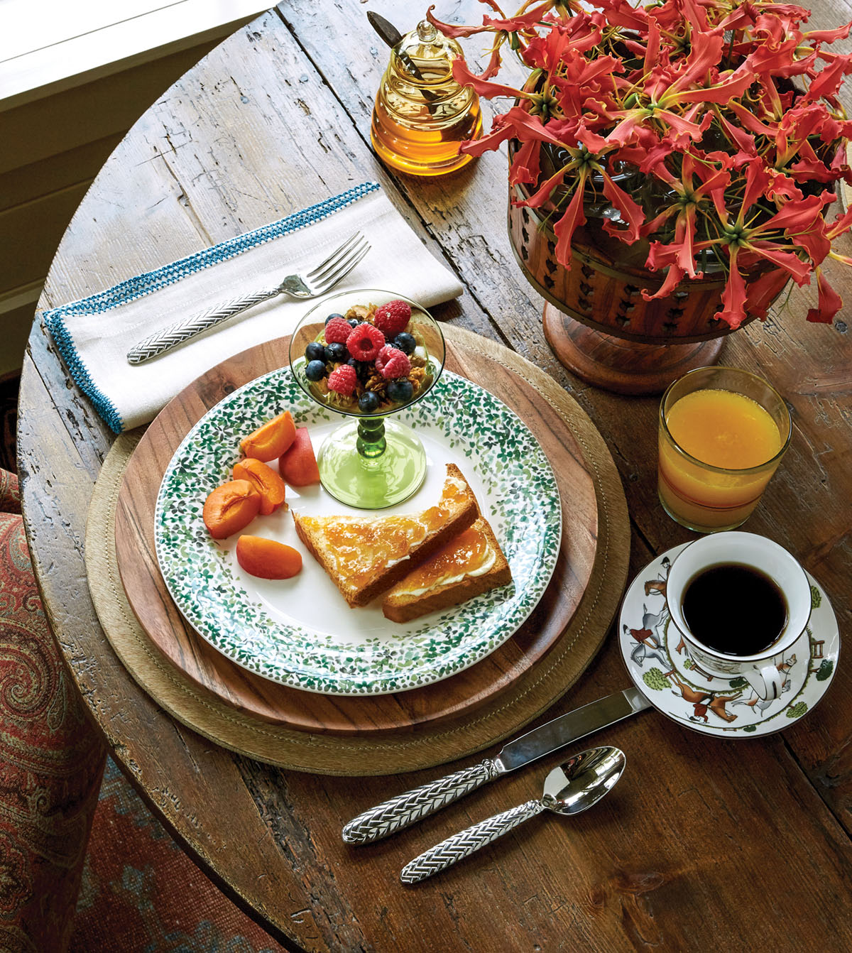 breakfast of toast, berries and granola, and sliced peaches set on a rustic wooden table