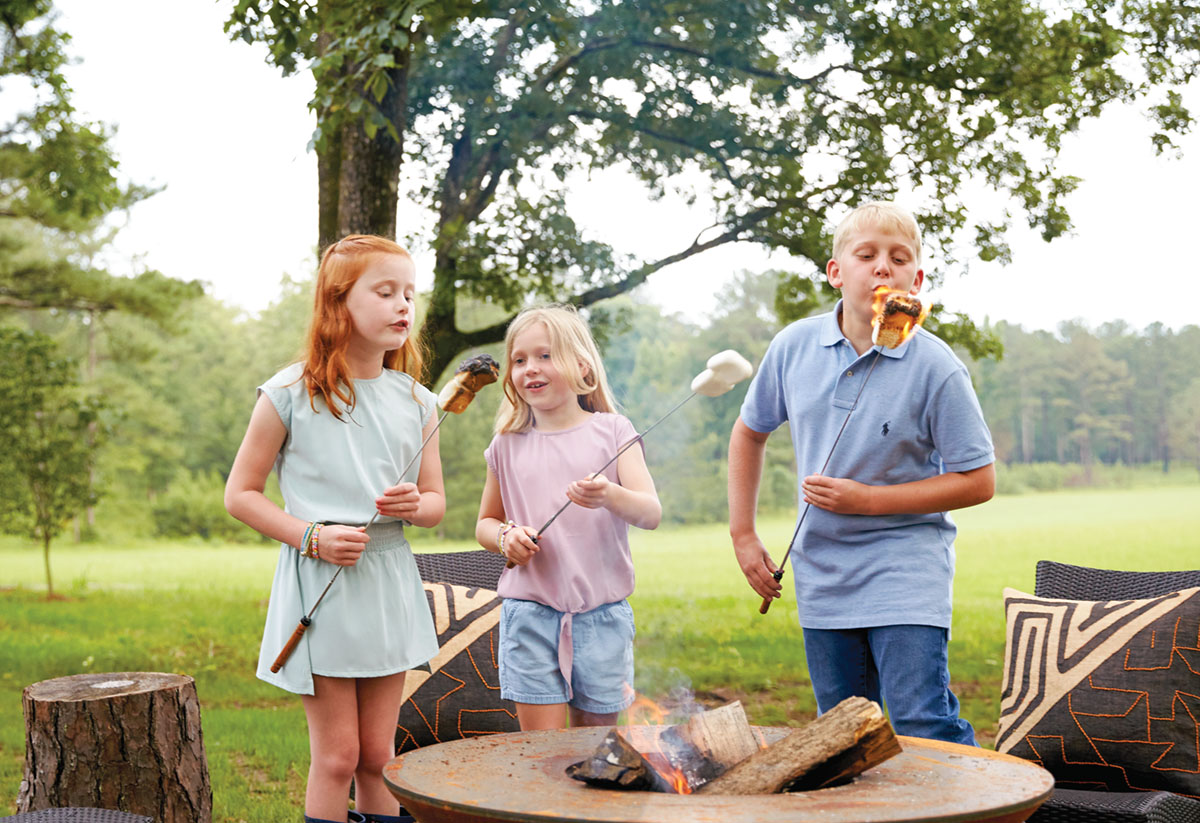 a trio of young children roast marshmallows over a firepit