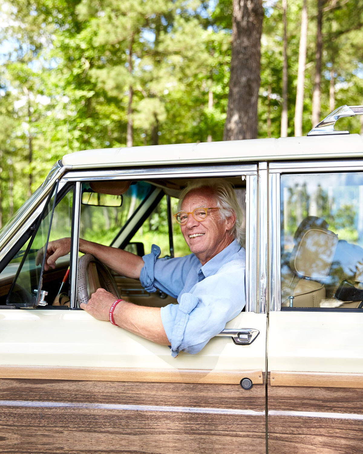 Gates Shaw, wearing a pale blue button up with the sleeves rolled up, smiles from the drivers seat of a vintage wood-panel car