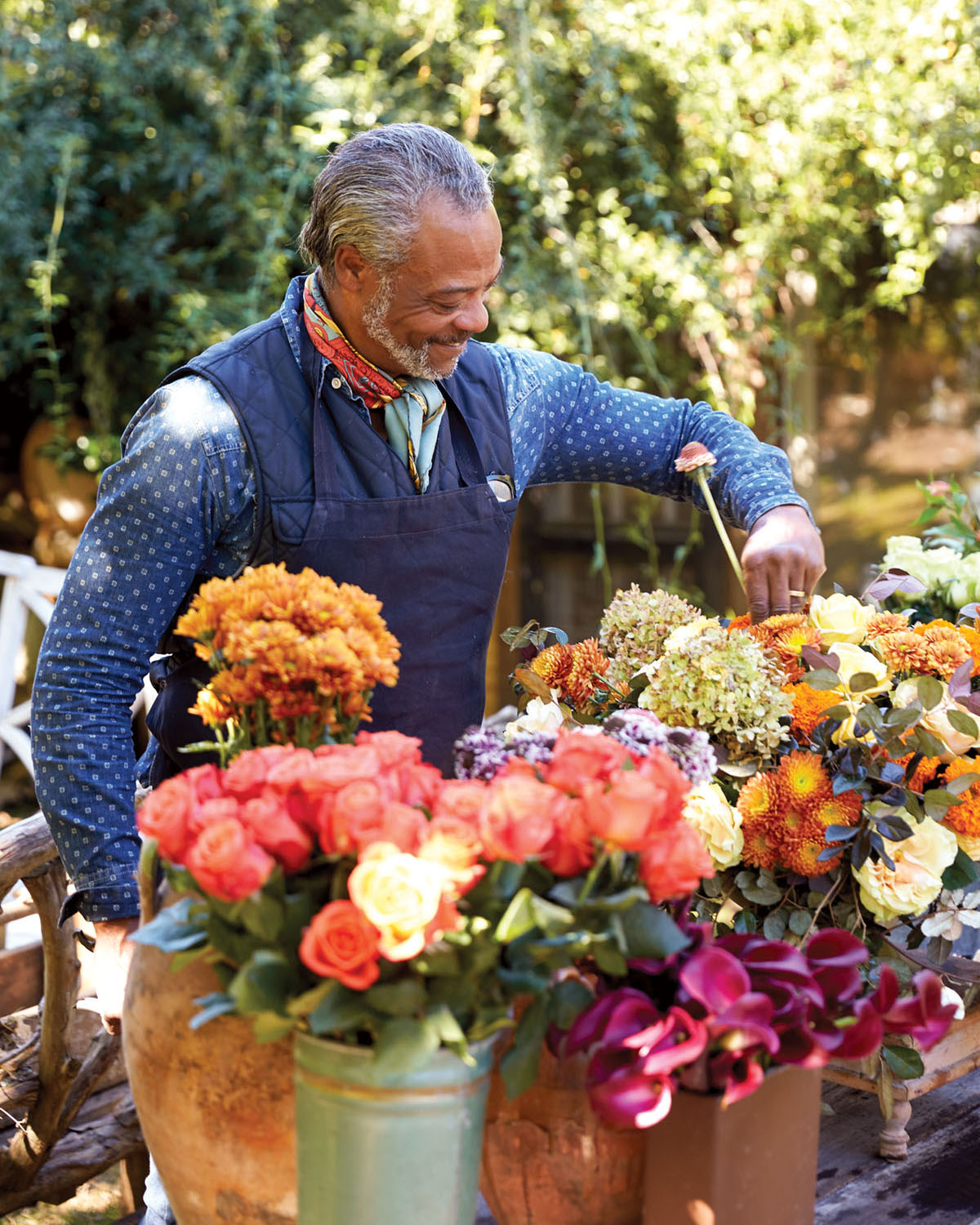 Keith Robinson, wearing a long-sleeved denim shirt, vest, and bandana around his neck, arranges fall flowers in a variety of coral and orange hues