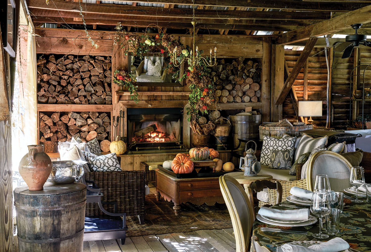 At Keith Robinson's home at Redwine Plantation, a large room with barnwood walls, floors, and ceilings. Ample firewood is stored in cubbies surrounding the hearth. Autumn floral arrangements, garlands, and pumpkins decorate the hearth and comfortable seating area.