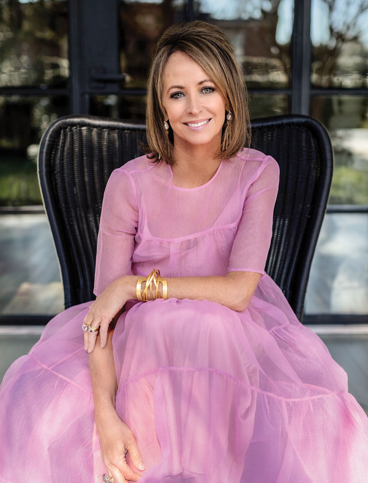 Inteiro designer Janie Molster wears a bright pink, long, flowy casual dresses, and sits in a black wicker chair outdoors