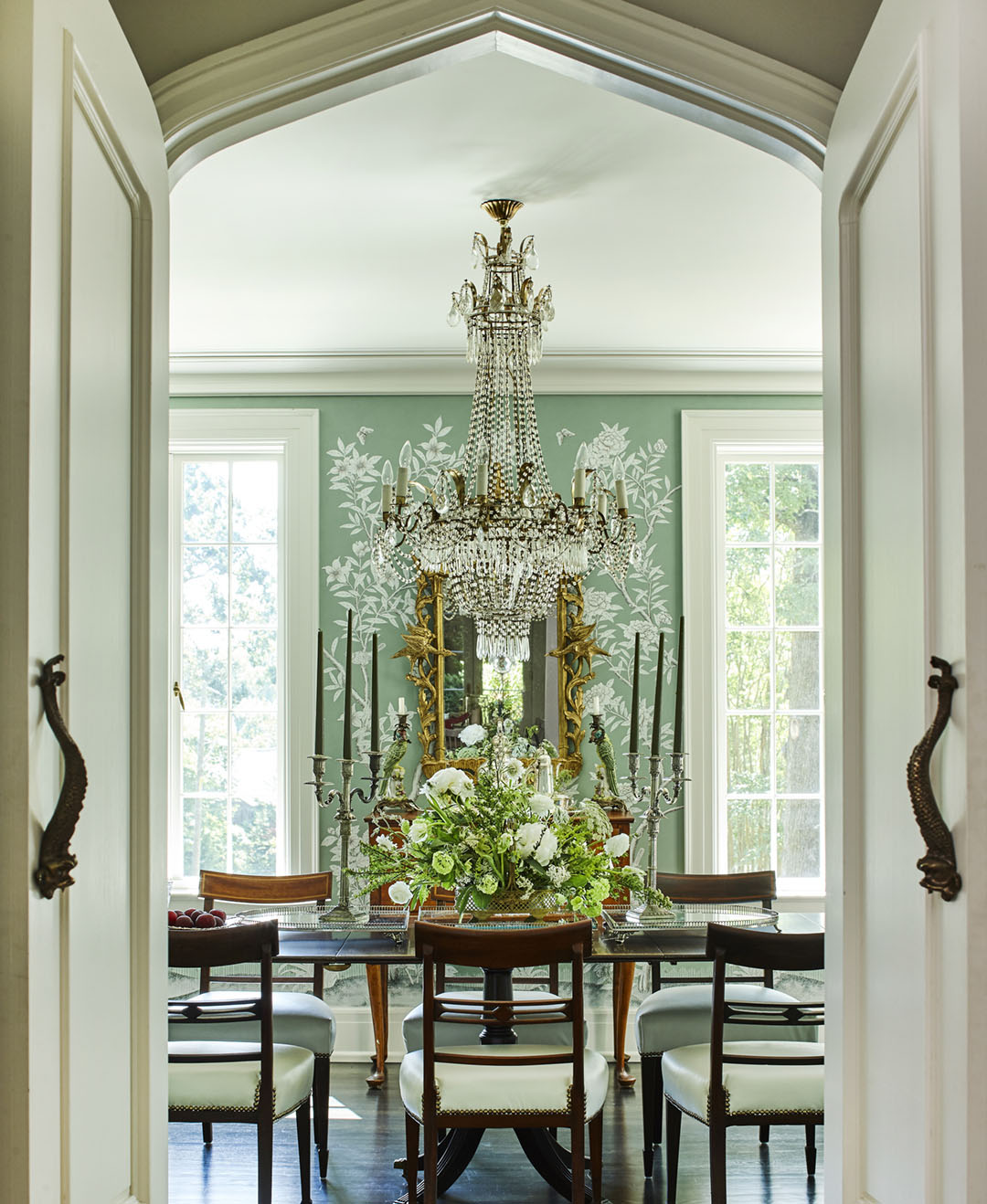 Double doors open to reveal a dining room papered in a custom, soft blue-green Gracie wallpaper, with an crystal chandelier and ornate gilt mirror