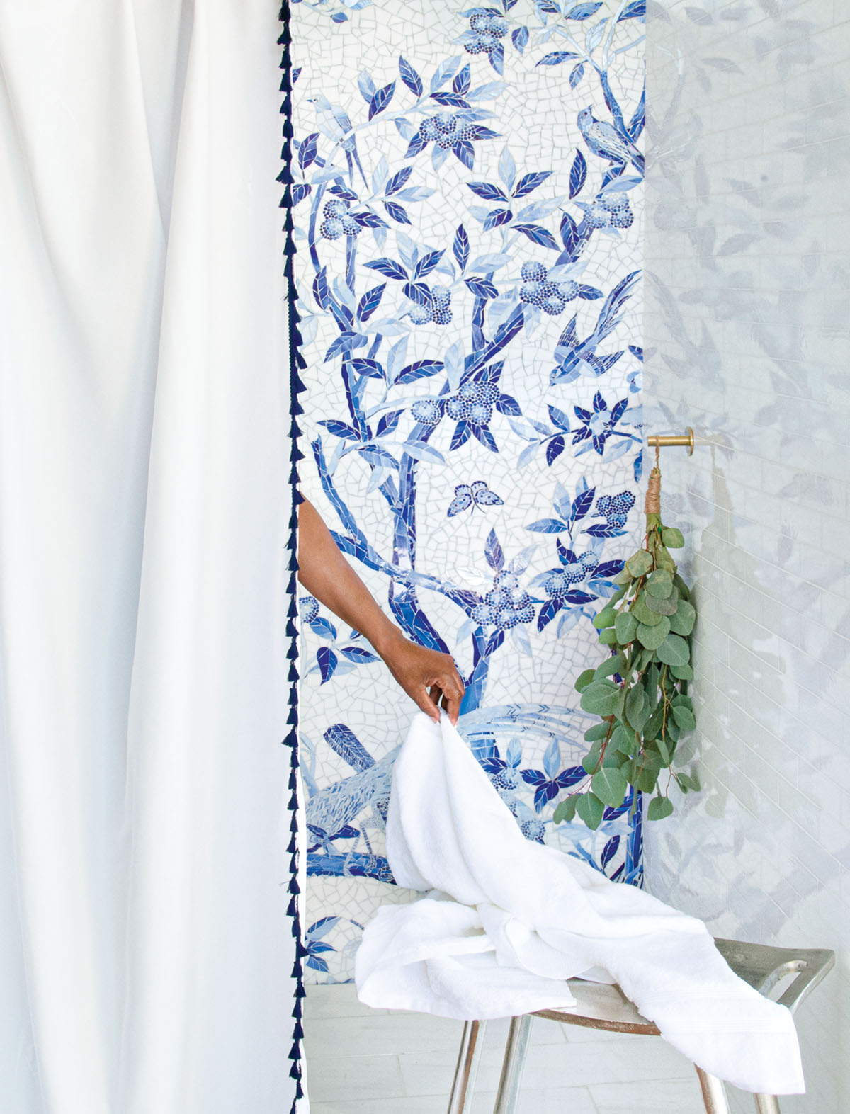 shower wall titled with a blue-and-white mosaic