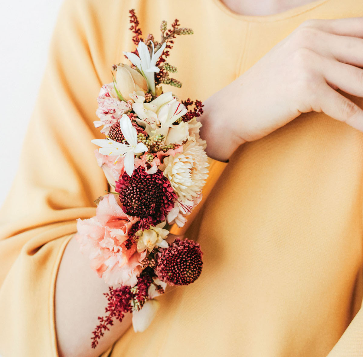 A model wears a floral cuff on her wrist featuring burgundy, cream, and peach-colored fresh flowers