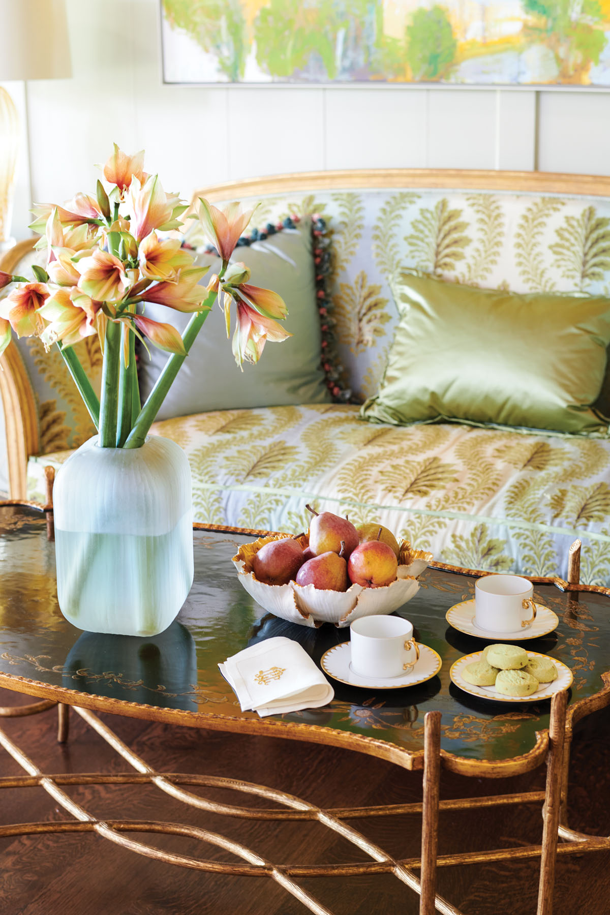 vignette with a settee, coffee table, vase of amaryllis in a frosted vase, bowl of pears, two cups/saucers, and cookiesa