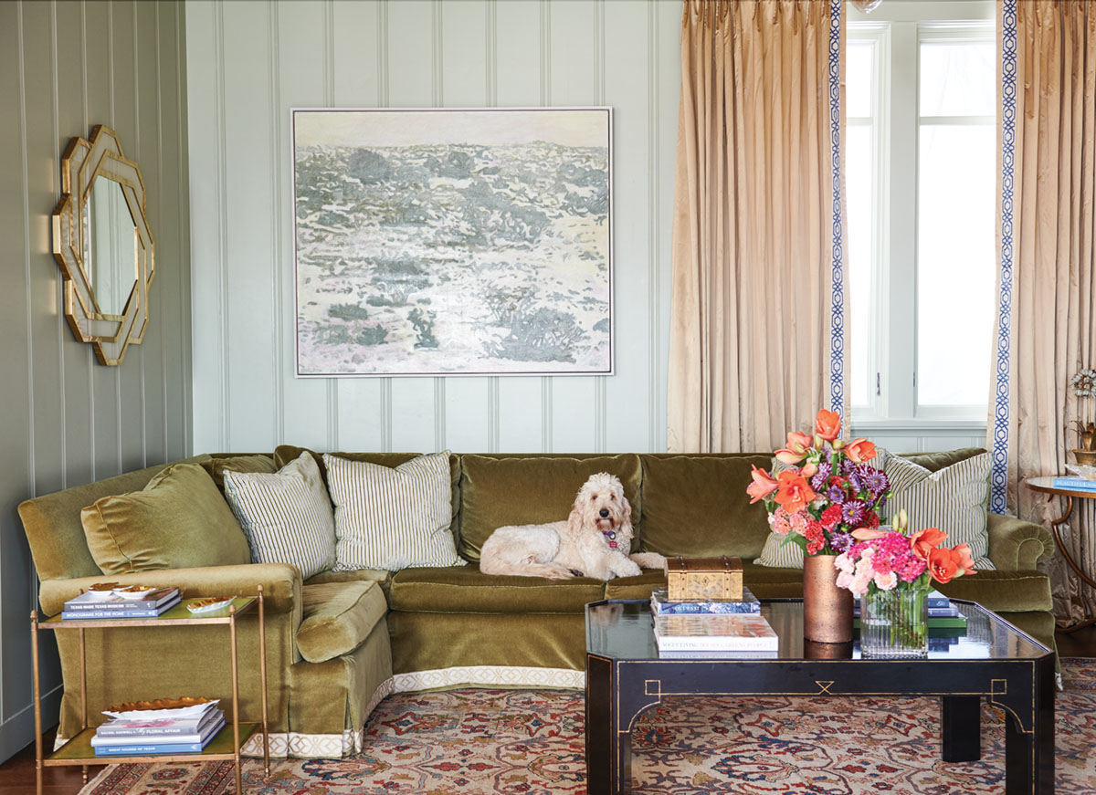 family room by interior designer Trish Sheats featuring paneled walls painted a soft gray-green, peach drapes, and an olive green sectional