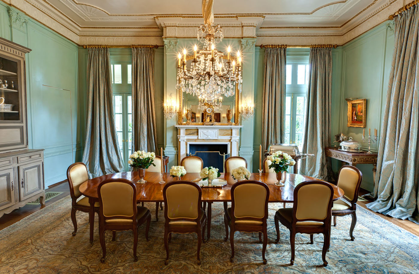 An elegant Robin's egg blue dining room with floor to ceiling taupe drapes, a crystal chandelier an antique rug in muted colors featuring an oriental rug pattern