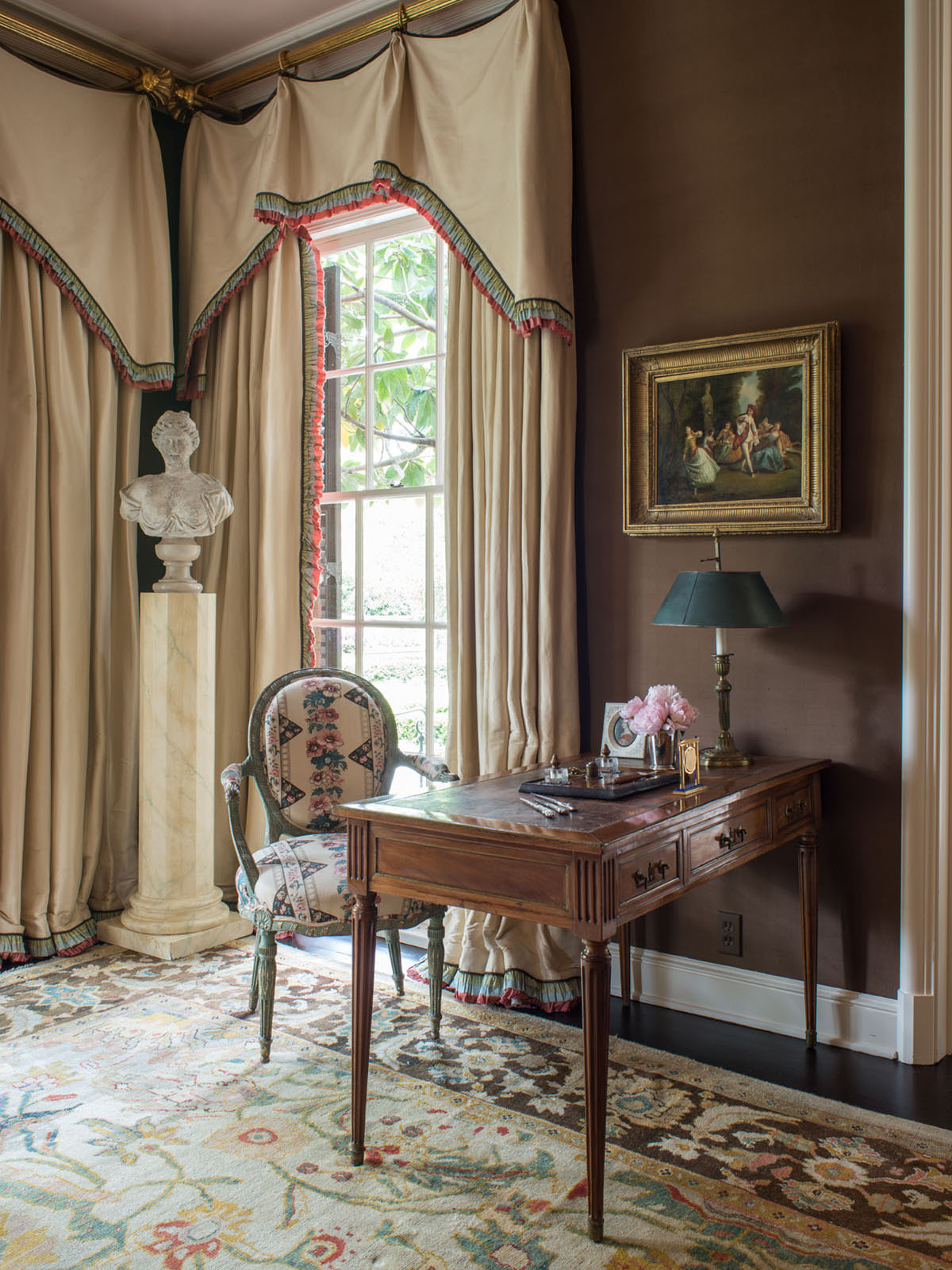 A study painted deep taupe features an antique desk and chair, a carved bust displayed on a pedestal, tailored valances and floor-to-ceiling drapes, and a Persian Sultanabad floral rug pattern, featuring yellow, coral, and green motifs on an cream background and dark brown border.