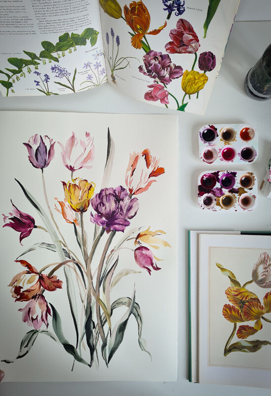 watercolor of spring bulb flowers by Safiyyah Choycha. Botanical reference books and watercolor paints show the artist's tools of the trade