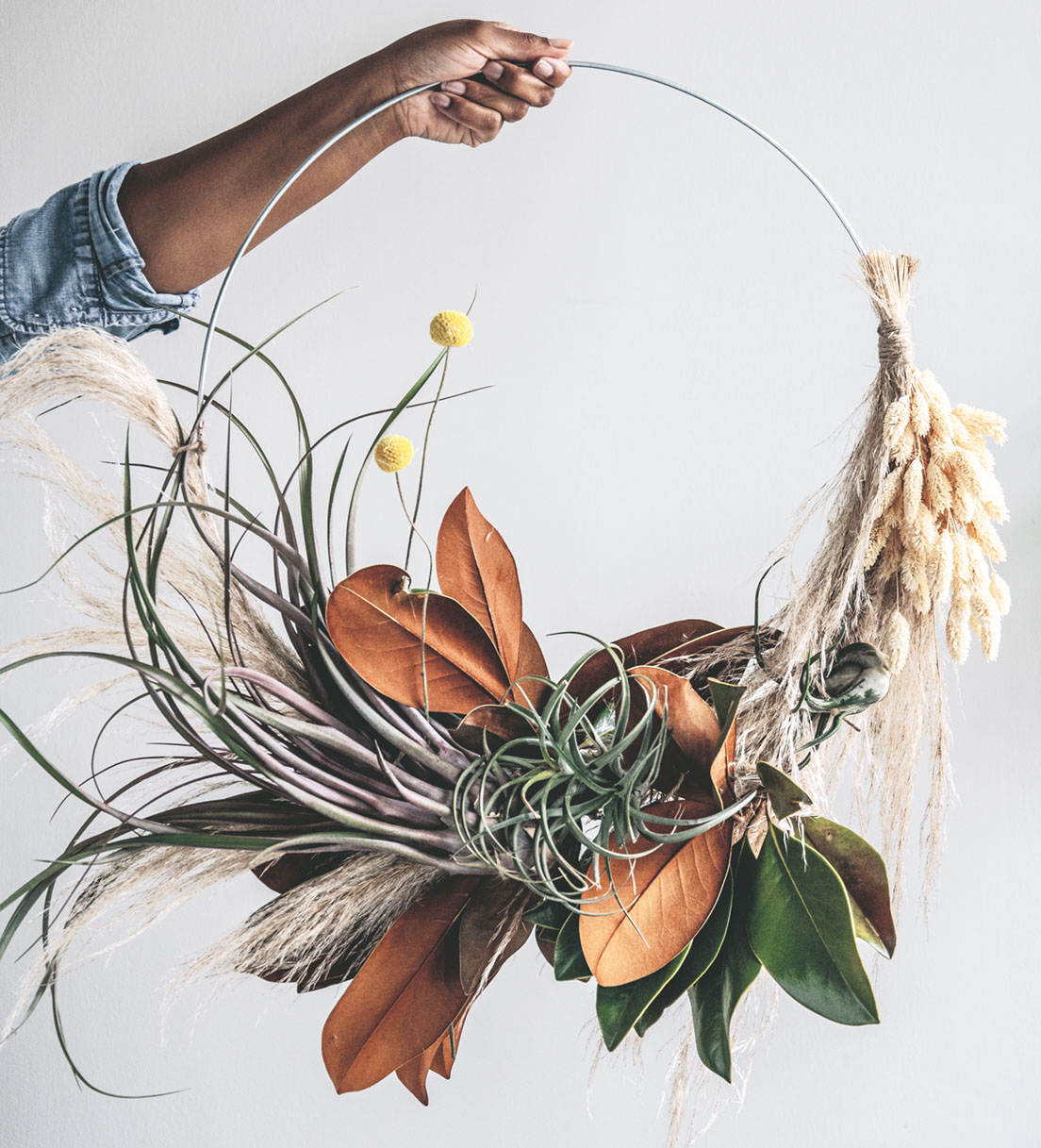 Hilton Carter's air plant wreath with magnolia foliage, pampas grass, bunny tails, and yellow billy balls