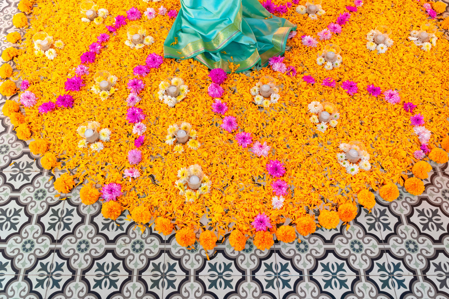 a vibrant circular, symmetrical design of orange marigold blooms and petals, accented with pink flowers, on an ornate tile floor