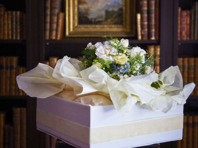 India Hicks's Wedding Party Flowers, bouquet set in tissue paper in a white box, with a moody English home library in the background