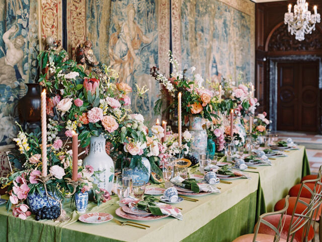 An opulent table filled with flowers and set on green velvet, set against the backdrop of Flemish tapestries at the Anderson House