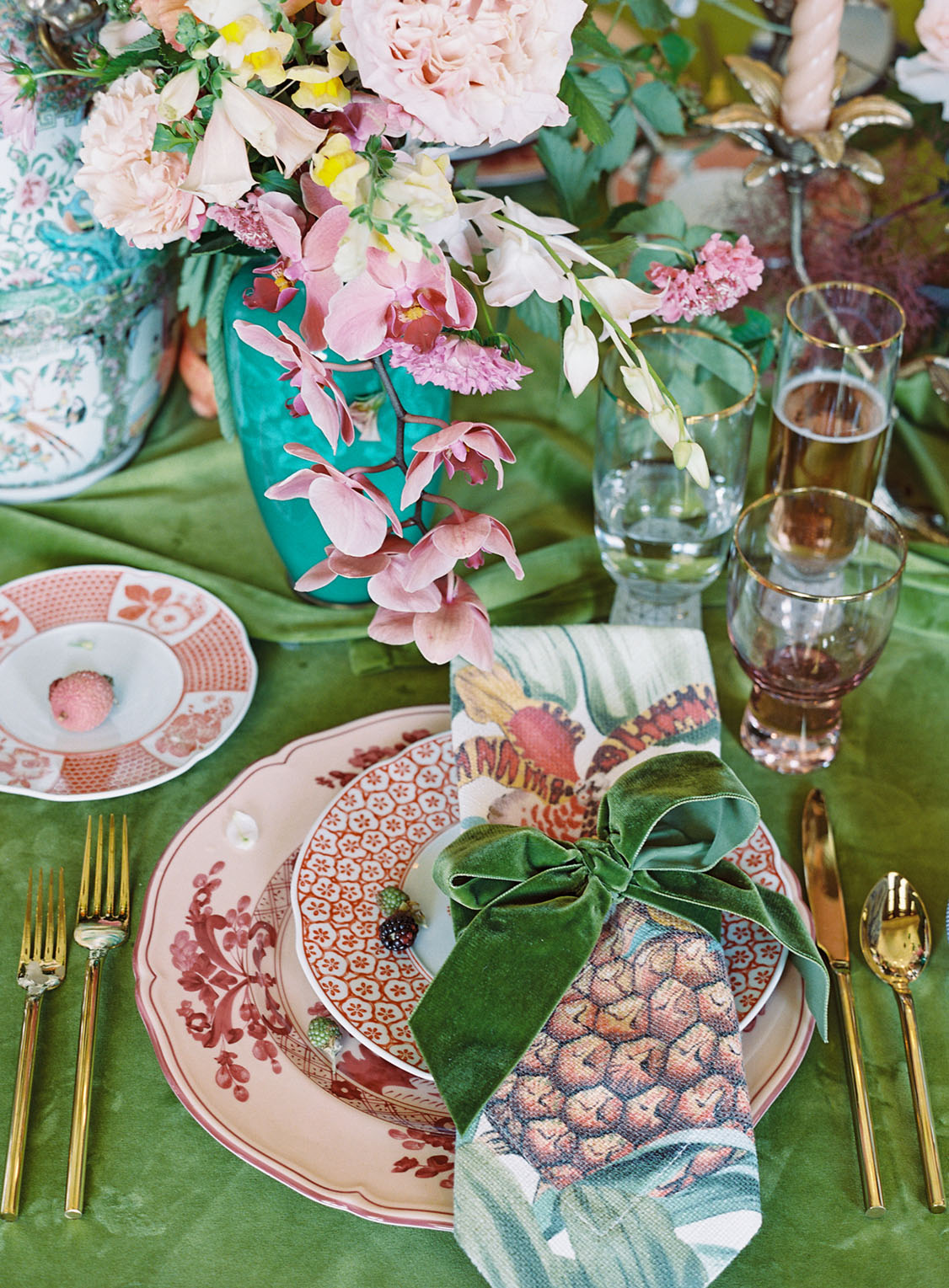Place setting with coral-colored dinnerware patters, gold flatware, a green velvet bow around a botanical-print napkin, and a green velvet tablecloth. Creative direction by Lustre Theory